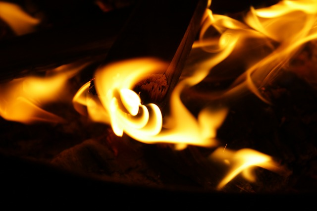 A close up on the orange flames of a fire on a dark background. For a post about Beltane.