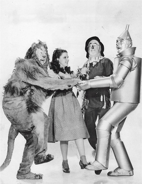 A screenshot from the film The Wizard of Oz in black and white, featuring the Cowardly Lion, Dorothy, the Scarecrow and the Tin Man