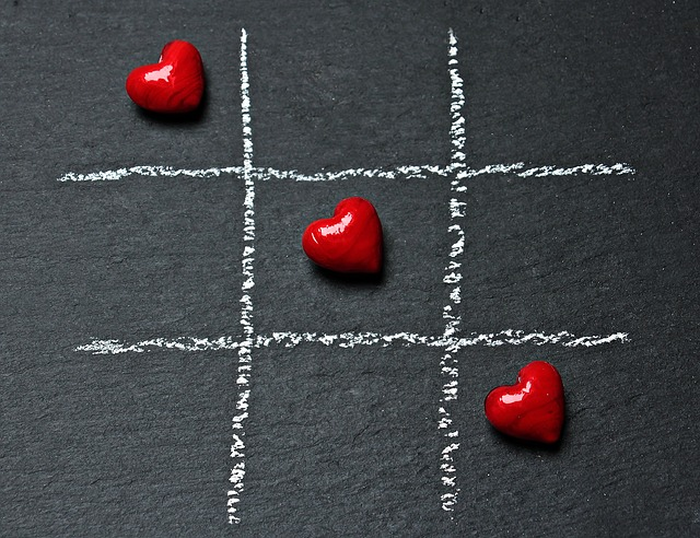 Three red hearts arranged diagonally across a tic tac toe board. For a post on polyamory and hierarchy