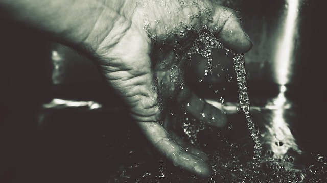 A black and white shot of a male hand under running water. For a post about fingering