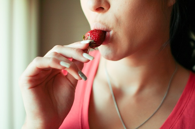 The lower half of a woman's face, sucking on a strawberry in a seductive fashion. For a post about foreplay