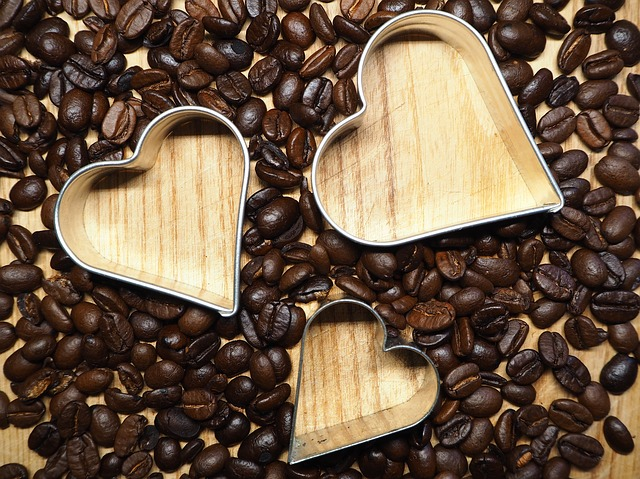 Coffee beans on a surface with three hearts cut out by cookie cutters. For a post about threesome