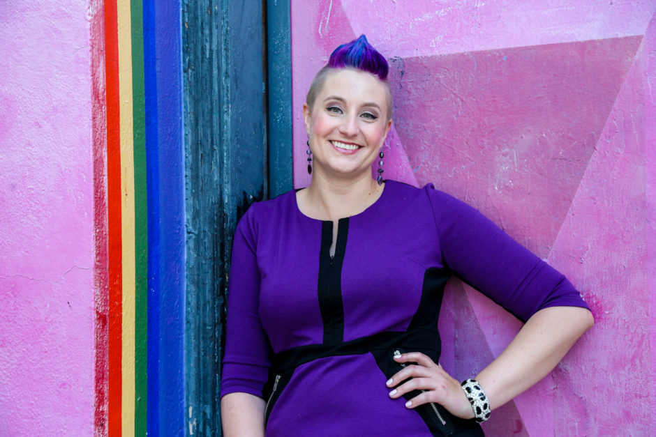 A photo of Dr Liz Powell wearing a purple dress and sporting short purple hair