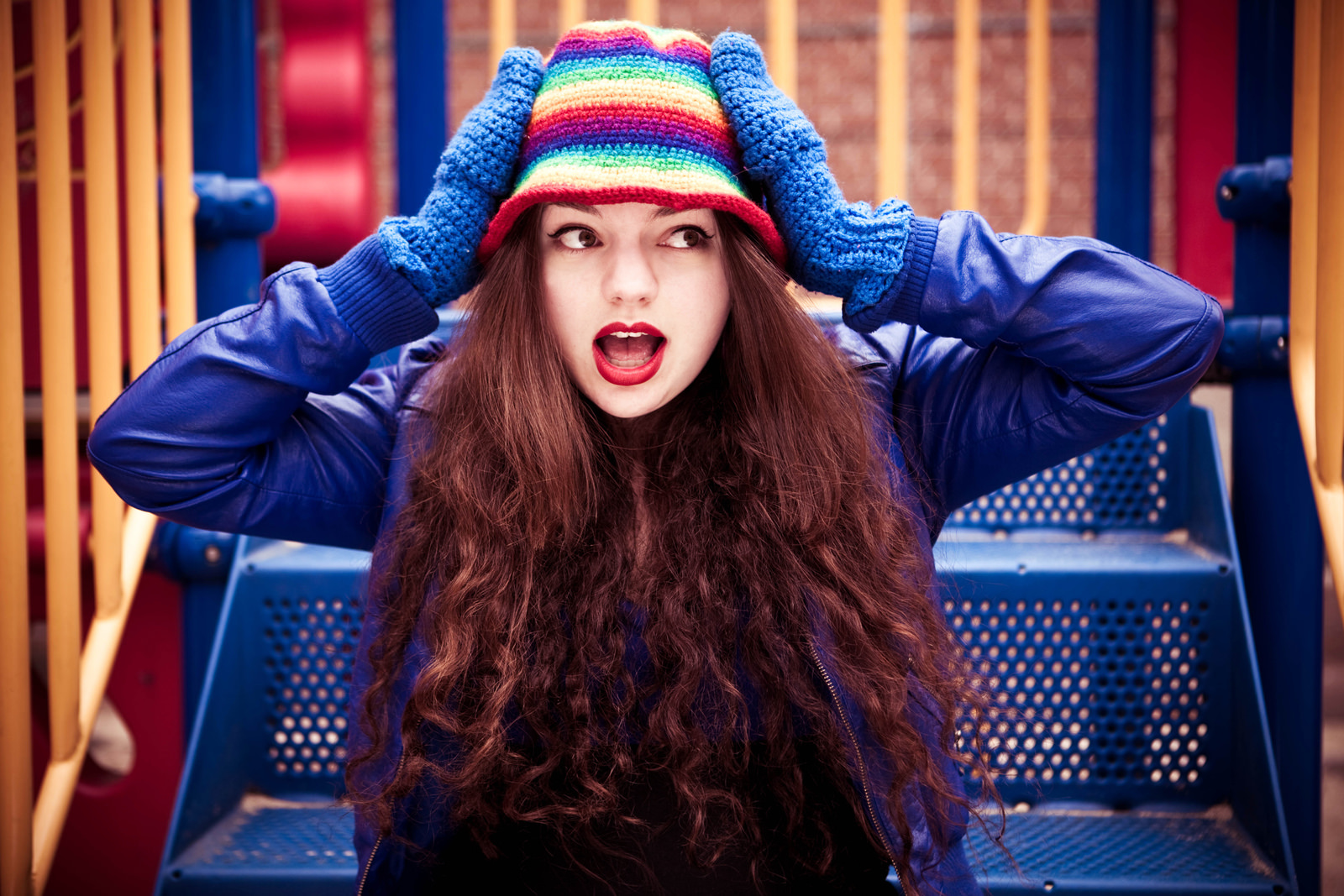 A picture of Kate Sloan, a white woman with long, wavy dark hair. She has her hands on the side of her head and her mouth open in a 'surprised' expression. She is wearing a blue jacket, blue gloves and a rainbow striped knitted hat.