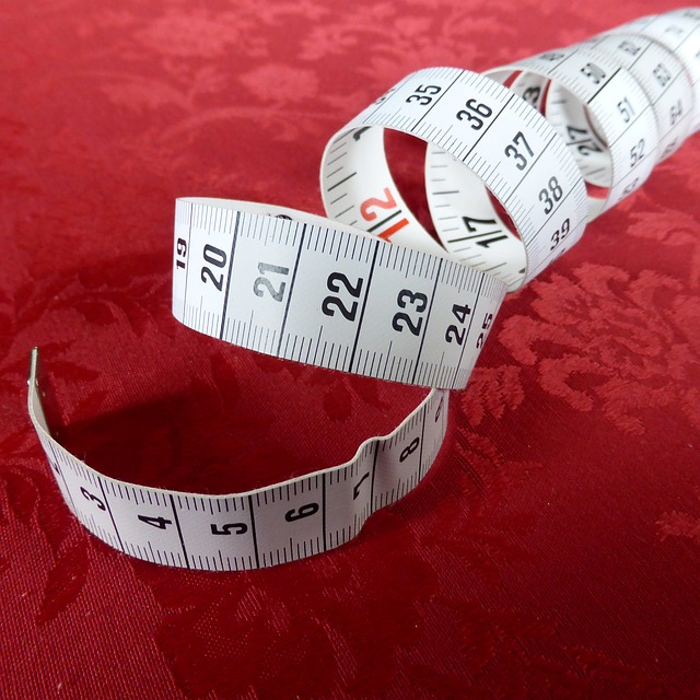 A half uncoiled tape measure on a red background. For a post on Dick Size with Exhibit A
