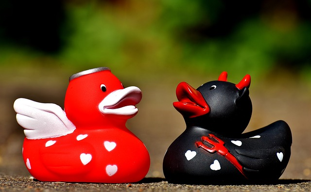 Two rubber ducks, one red and decorated like an angel, and one black and decorated as a devil. For a post on submissive archetypes.