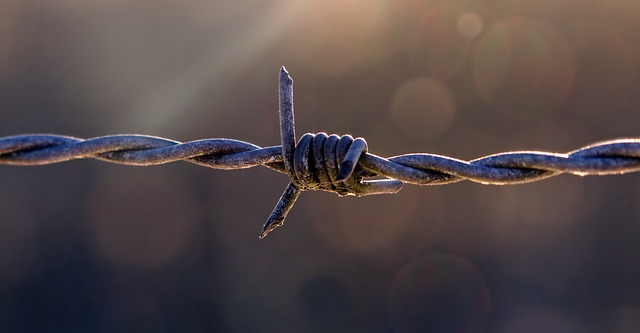 A close up on a section of a barbed wire fence for a post about hard limits