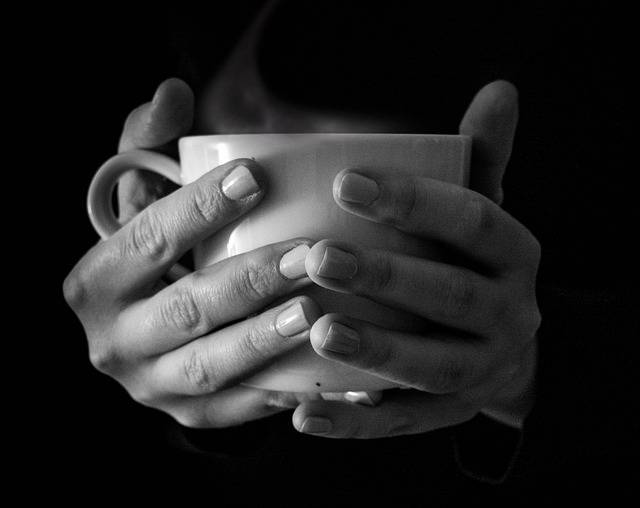 A pair of hands offering a steaming mug, in black and white. For a post on tasks and rituals.