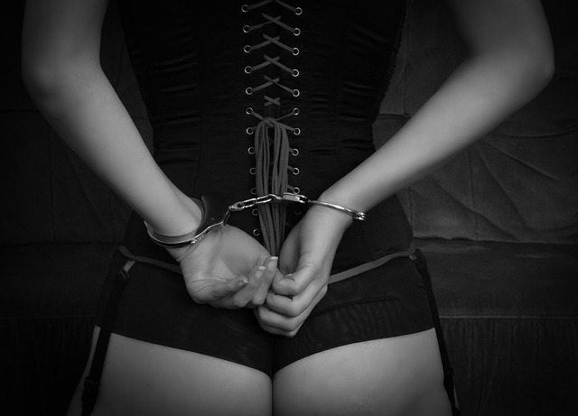 A woman's upper body and bottom from the back, with her hands cuffed behind her back. Black and white. For a post about subspace