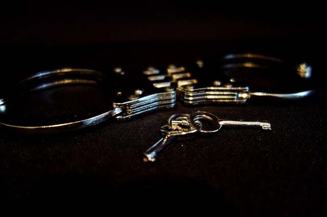 A close up on a pair of metal handcuffs and keys. For a post on things that don't make you less dominant