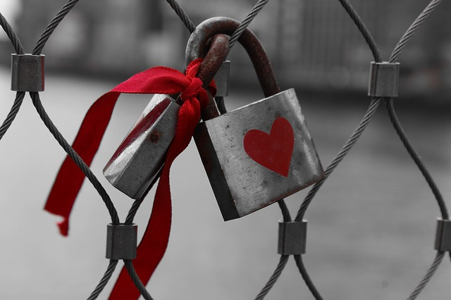 A padlock with a red heart on it and a red ribbon tied to it, fastened to a wire fence. For a post on 24/7 D/s