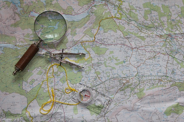 A close up on a map, magnifying glass and compass. For a post on exploring kinks and when they don't work.