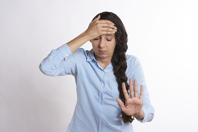 A white female-read person with long dark hair wearing a blue shirt. They have their hand to their forehead and a stressed expression on their face. For a post about sex in difficult times.