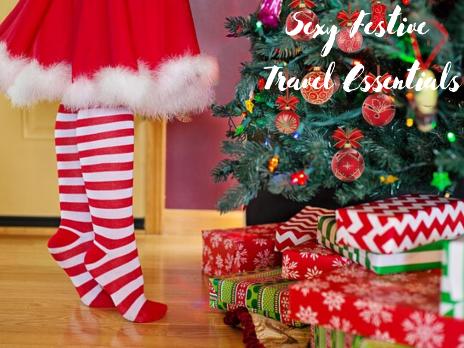 A woman in stripy stockings and a santa dress on tiptoe by a Christmas tree. For a post about sexy festive travel essentials