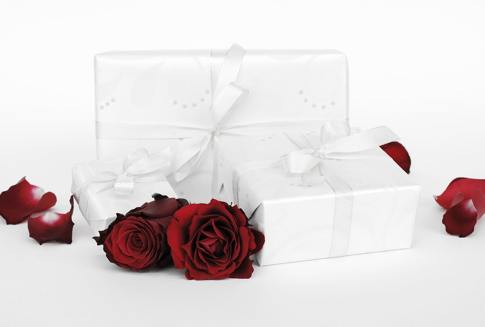 Two red roses and three boxes wrapped in white gift paper. For a post about buying sex toys for Valentine's Day.