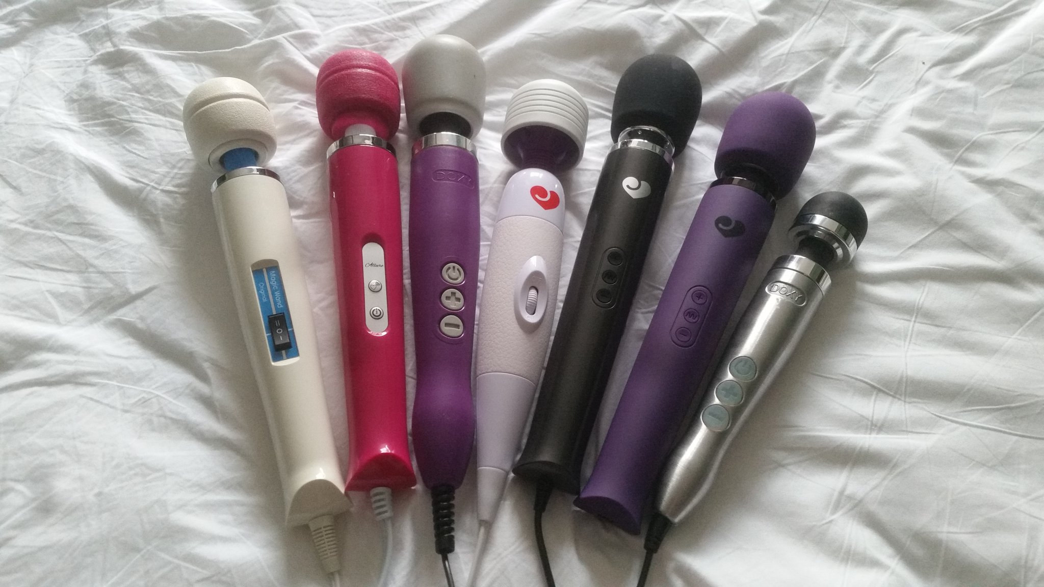 All seven of the wand vibrators I own lying on my bed on a white sheet.