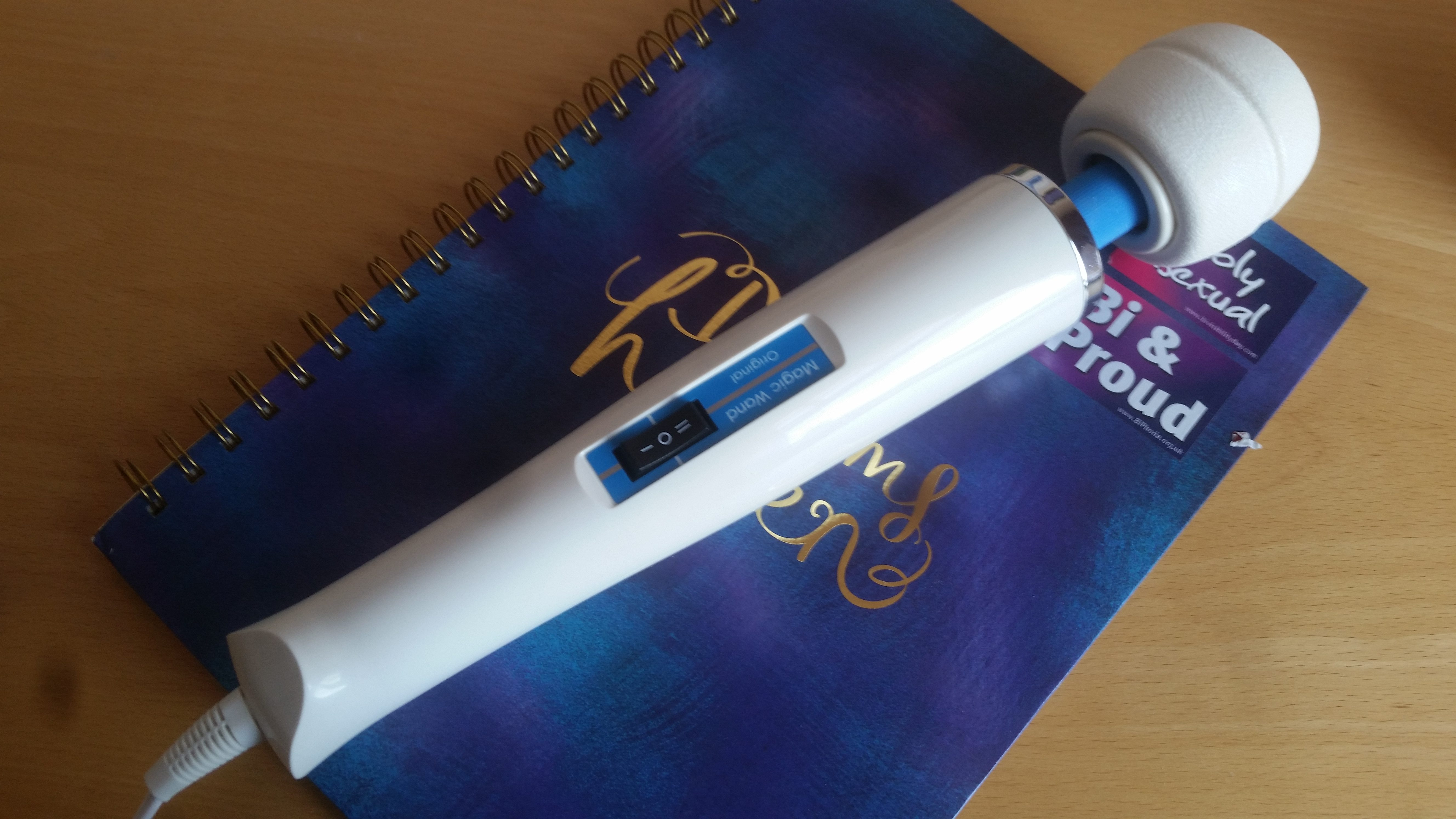 The Hitachi Magic Wand Original, lying on a blue notebook covered in bi pride stickers.