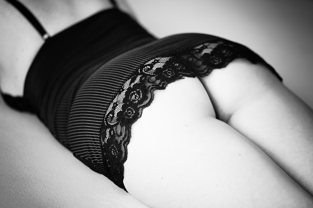 A woman lying face down on a bed wearing a black top with a lacy bottom, her butt on display. For a piece of schoolmaster cane erotica.