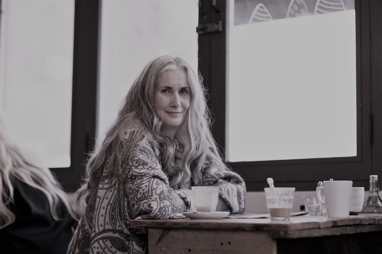 A pretty older woman with long flowing hair, wearing a patterned shirt. Sitting at a table with a mug in front of her, smiling into the camera. By Hot Octopuss, for a post on antidepressants and sex.