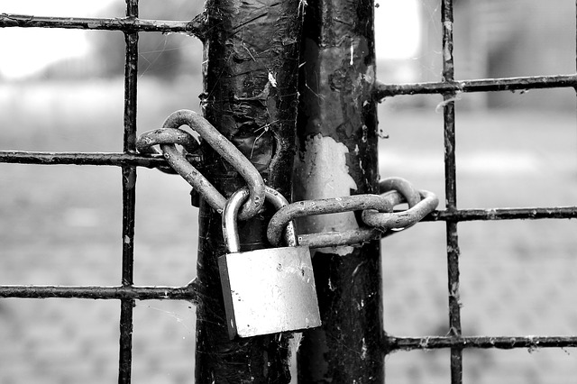 A black and white close up of a padlock and claim on the door of a cage. For a Masturbation Monday story called Fluff