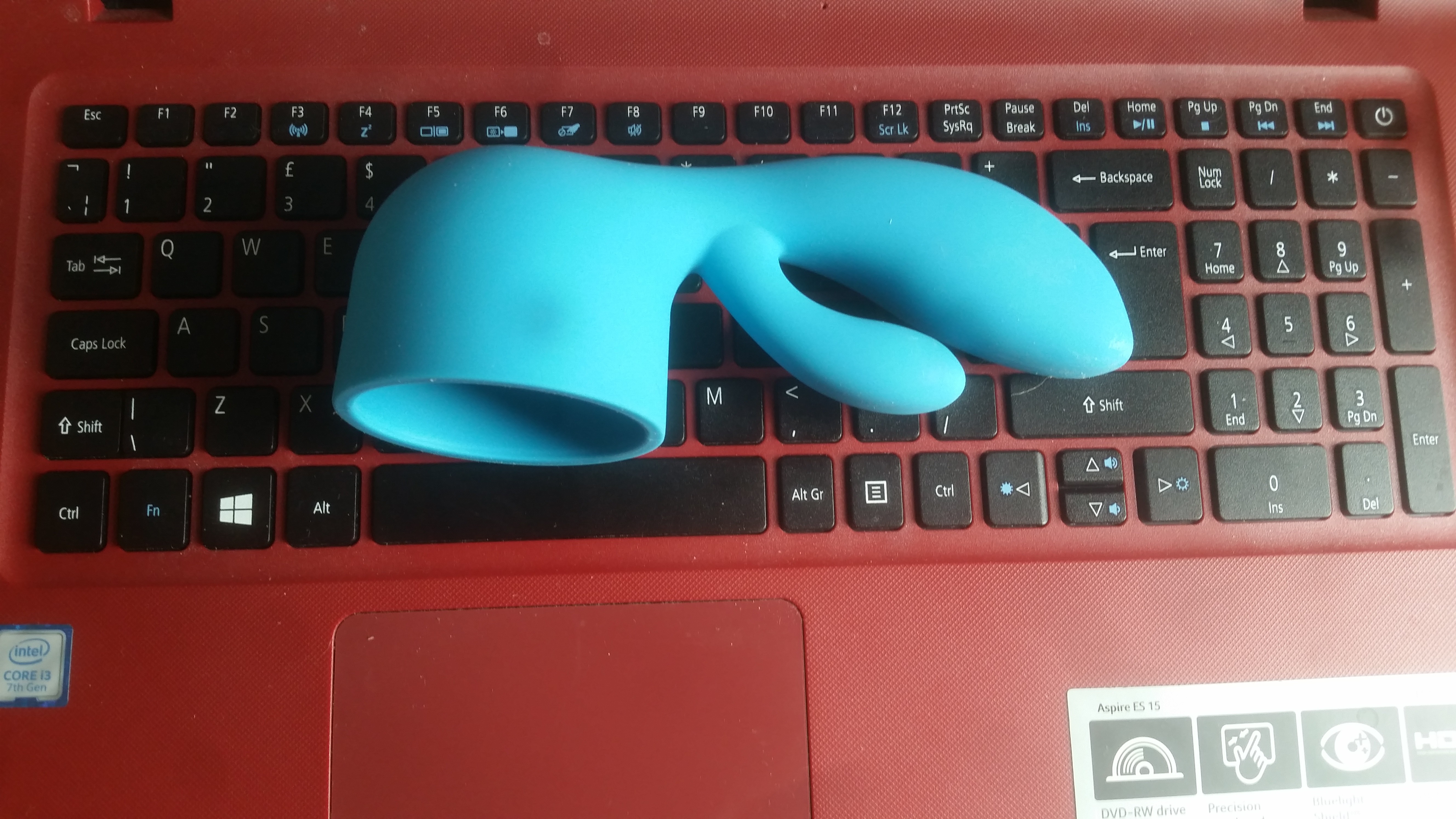 The bodywand blue silicone rabbit wand attachment sitting on a red and black laptop keyboard.