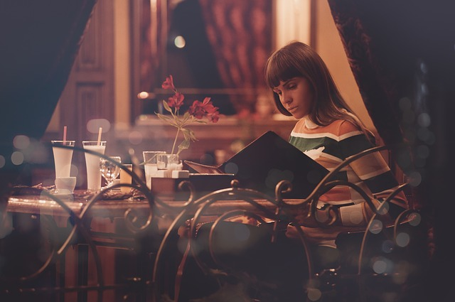 "A woman sitting alone reading at a restaurant table. For a Masturbation Monday piece called ""Dining Alone""."