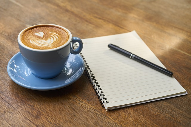 A mug of coffee, notebook and pen on a wooden surface. For a post about Smutathon 2018
