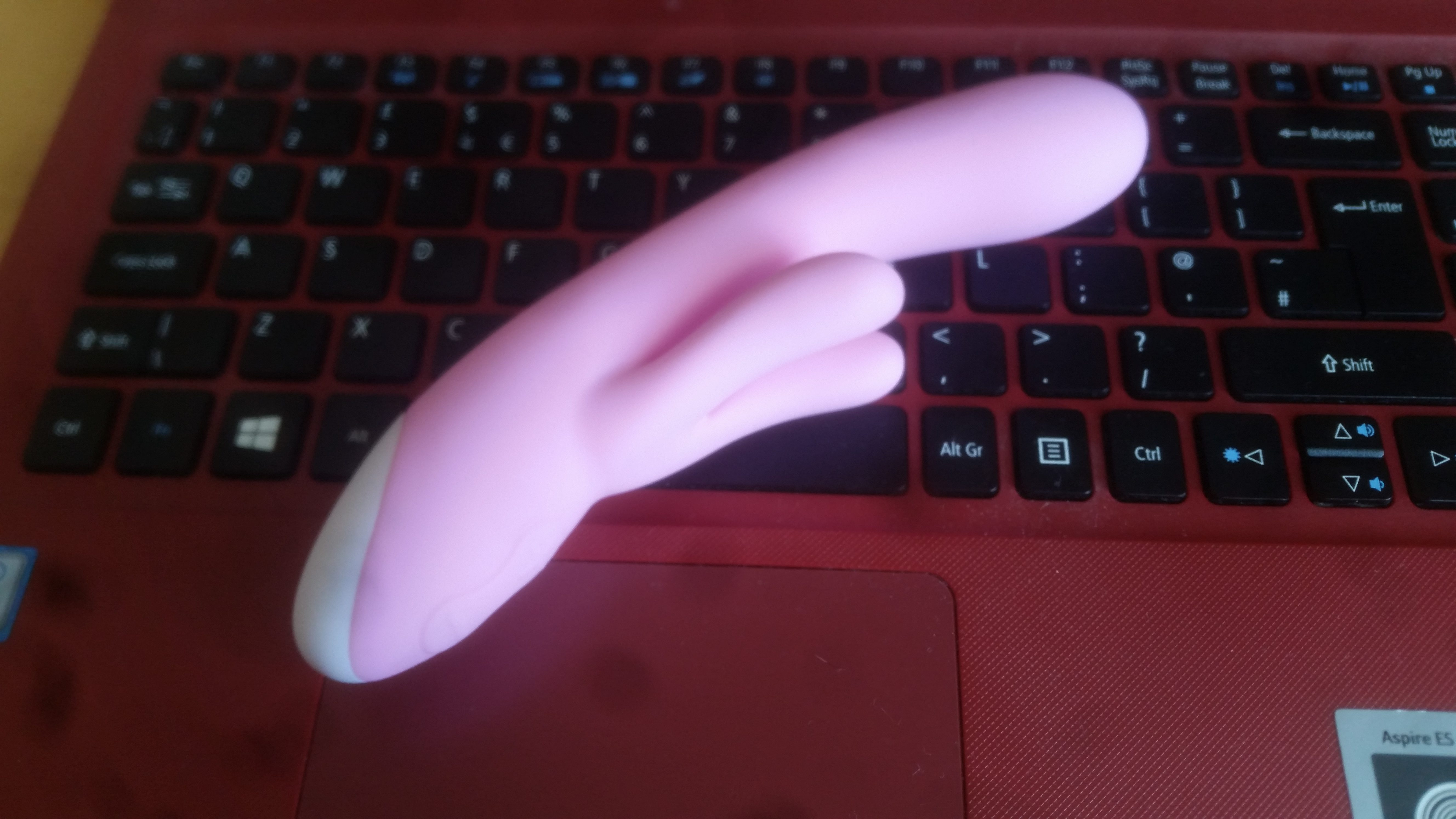 A pink rabbit vibrator lying on a red and black laptop keyboard.