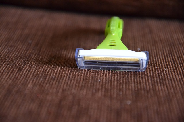 A green razor on a brown surface. For a post about body hair