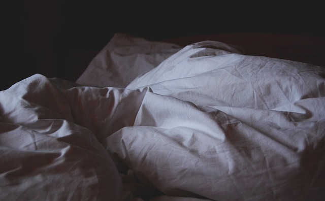 A bed with dim lighting and rumpled sheets. For a post on group sex