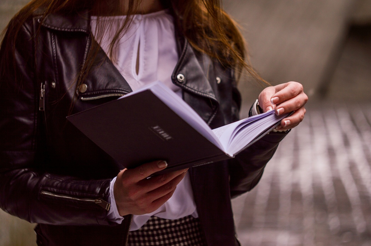 A woman reading a book pictured from shoulders to hips. For a post about erotica