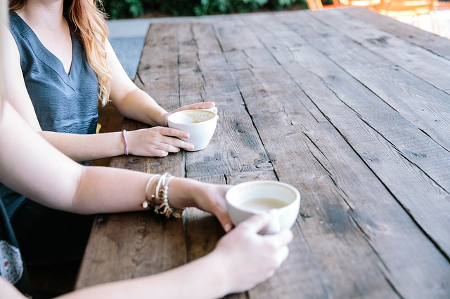 Two women drinking coffee at an outside table. Only their arms are visible. For a post on flirting as a queer woman.