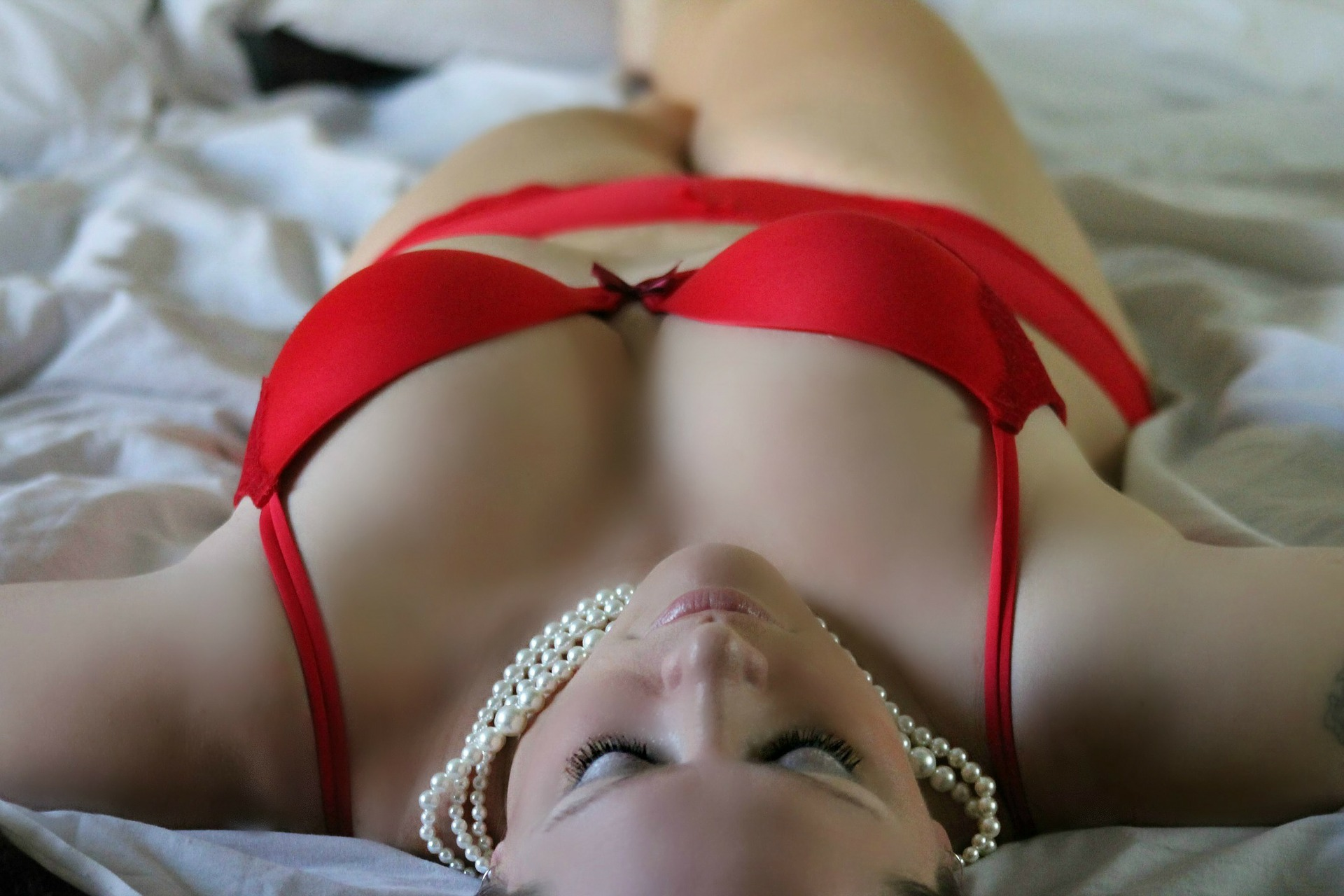 A woman reclining on a bed wearing red lingerie and pearls. For a sponsored post for Baby Jane LIngerie.