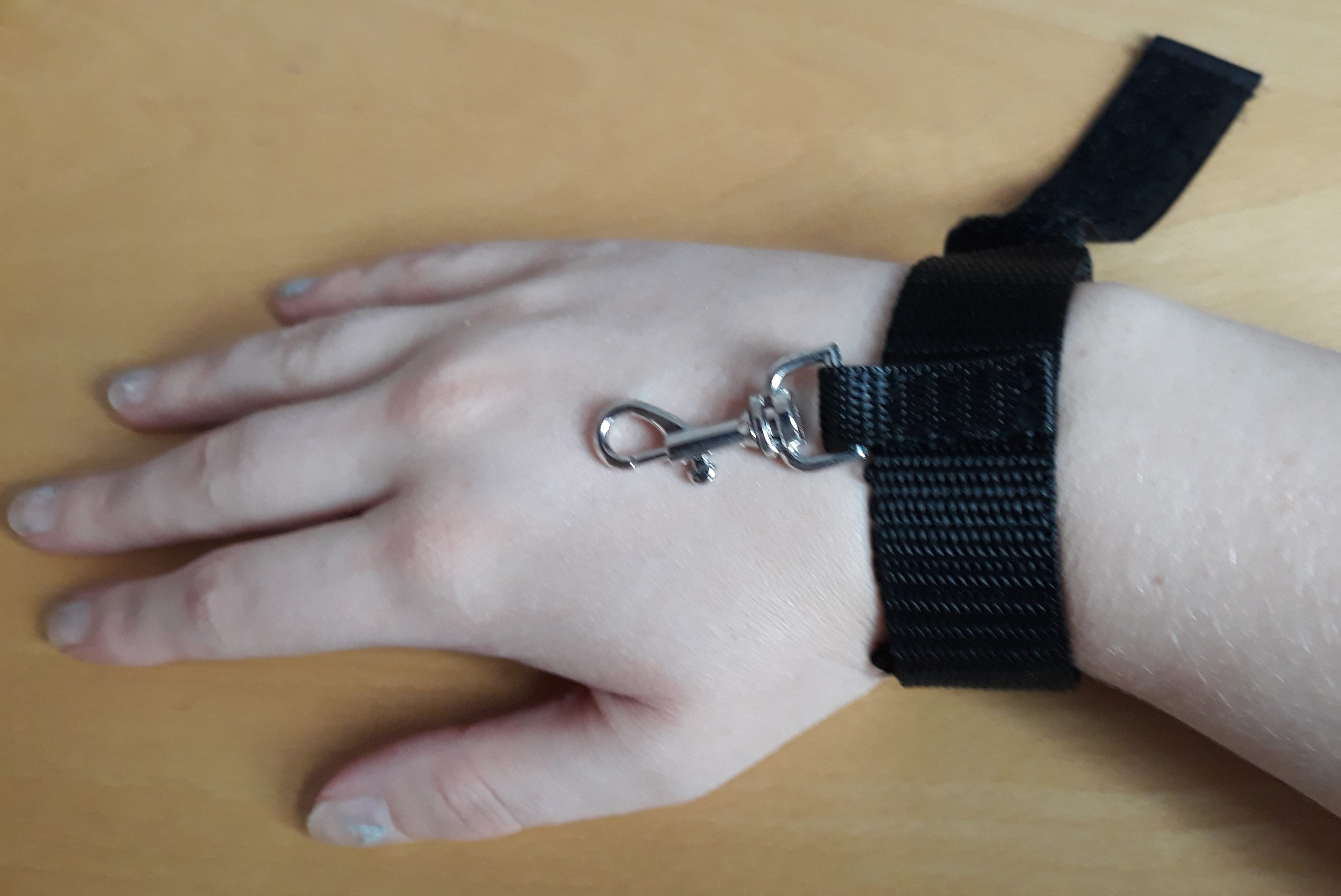 A woman's hand in a black velcro cuff. For a post about the Take Control bondage kit.