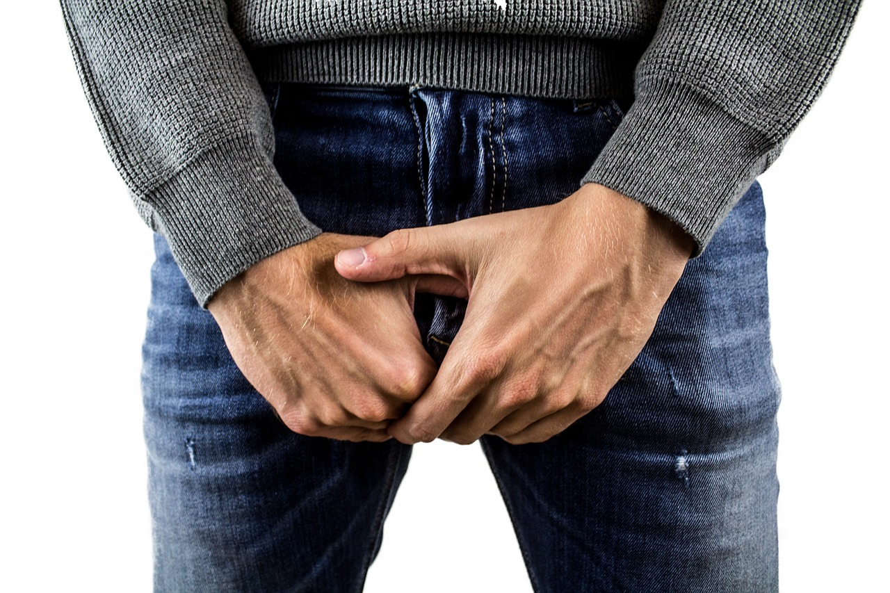 A man wearing blue jeans with his hands over his genital area, for a post about men struggling to reach climax