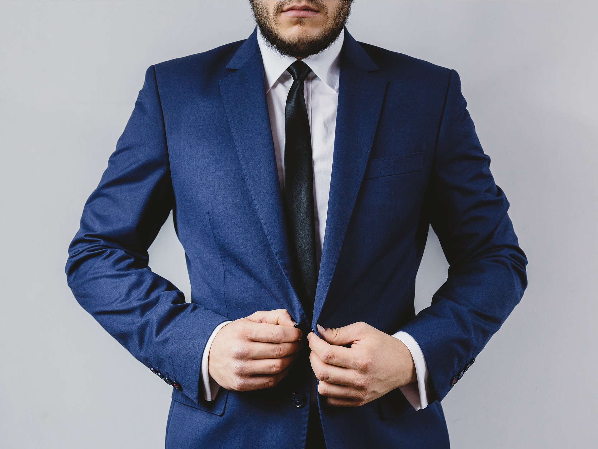 A man's body in a blue blazer and black tie. For an International Men's Day post on positive masculinity in erotica.