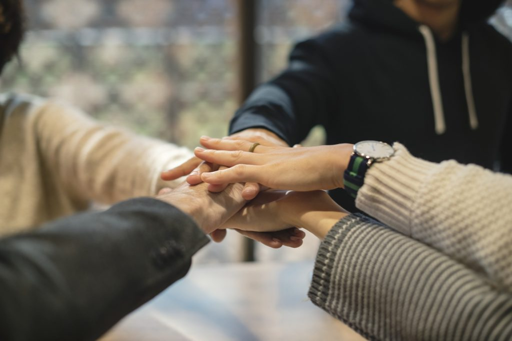A group of people putting their hands in a circle. For a post about making friends.