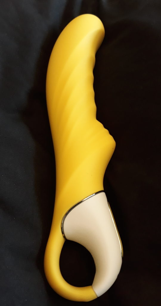The Yummy Sunshine vibrator on a black pillow