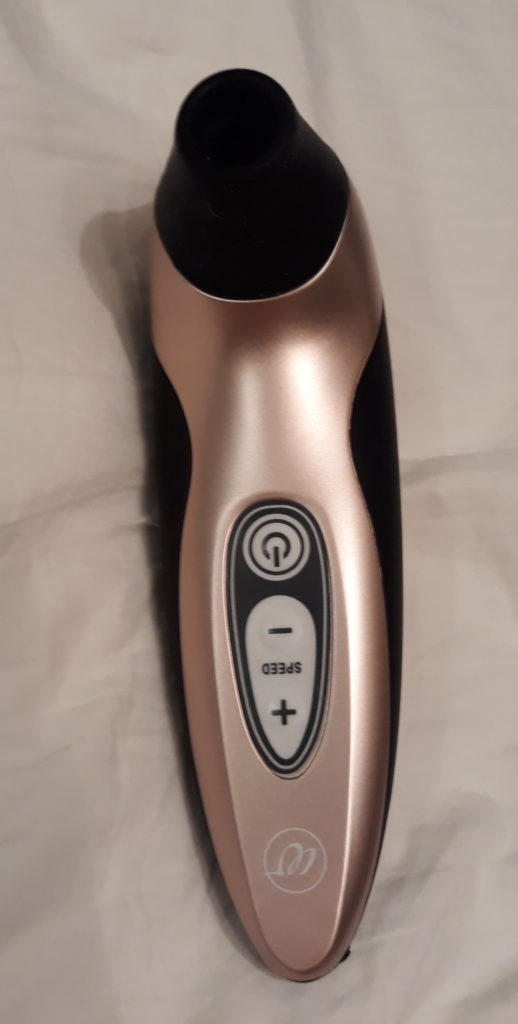 The Womanizer Pro40 black and rose gold clitoral suction toy lying on a white bedsheet.