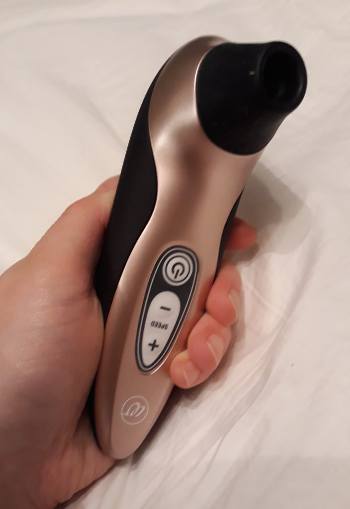 The Womanizer Pro40 black and rose gold clitoral suction toy in my hand on the background of a white bedsheet.