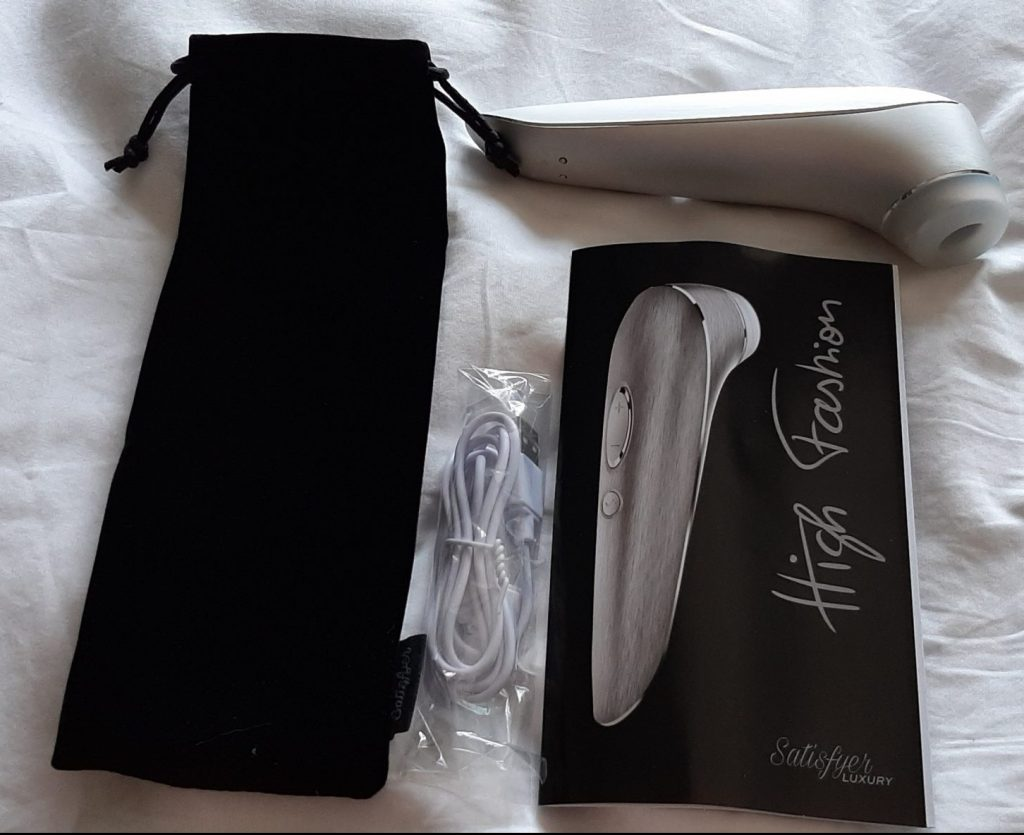 The Satisfyer High Fashion with charging cable, instruction booklet and storage pouch
