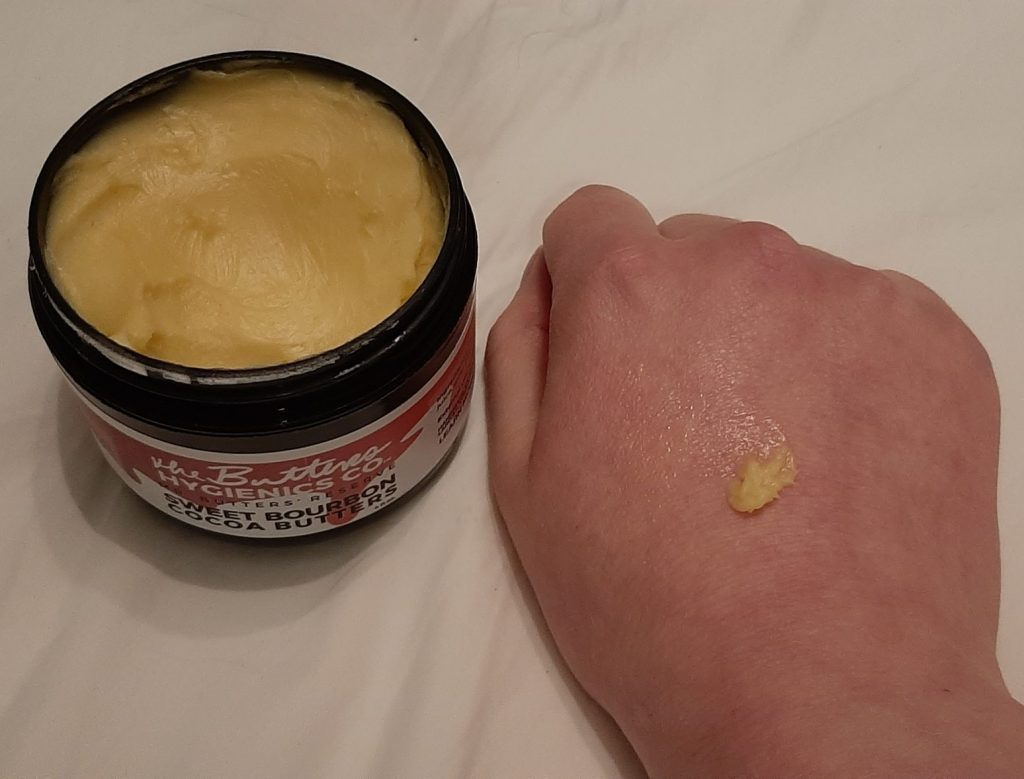 Yellow shea butter moisturiser on womans hand