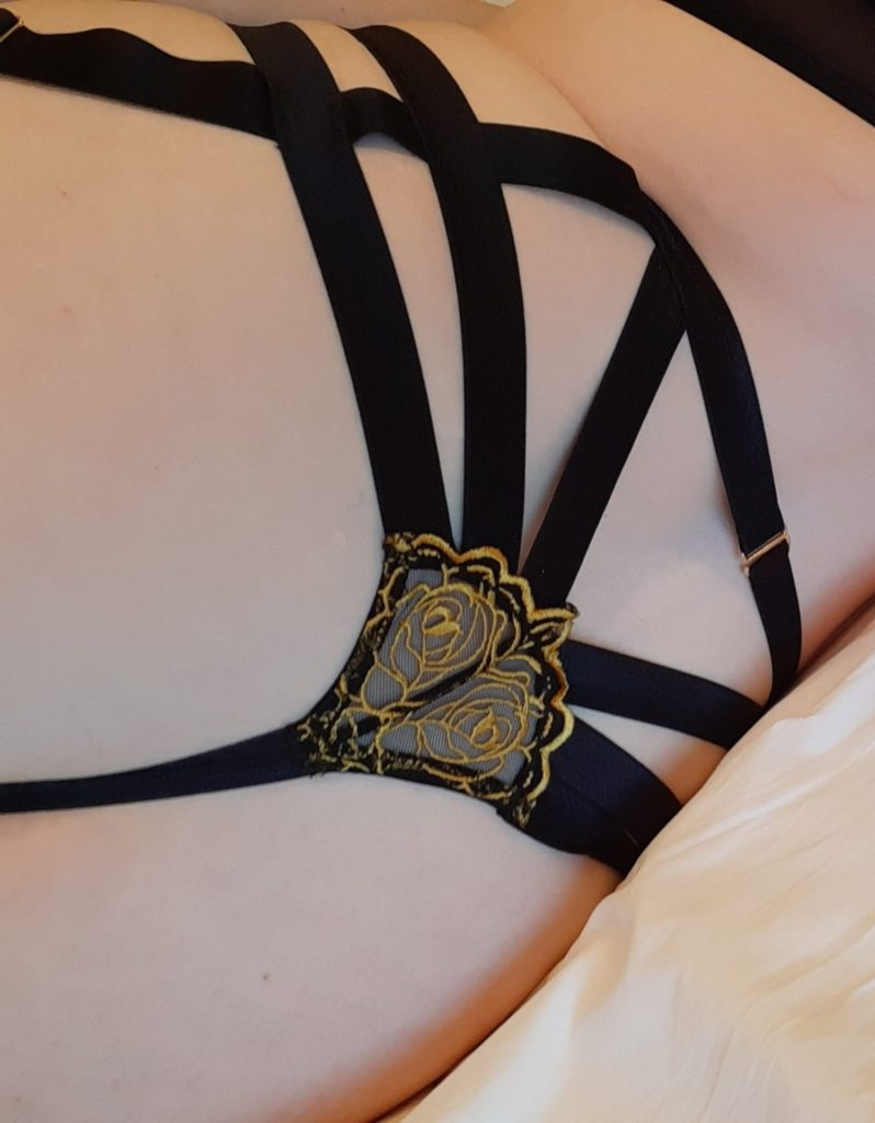 Womans butt in black and gold thong